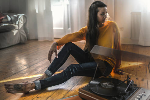 Young woman sitting on the floor at home with a record player - RIBF01023