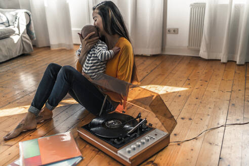 Mother with baby sitting on the floor at home with a record player - RIBF01026