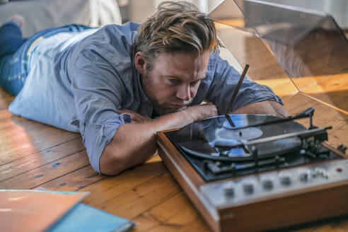 Man lying on the floor at home with a record player - RIBF01029