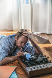 Man lying on the floor at home with a record player - RIBF01032