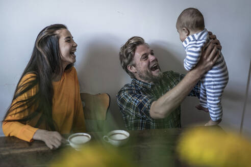 Happy family with baby sitting at wooden table at home - RIBF01041