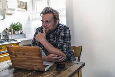 Man using laptop on kitchen table - RIBF01050