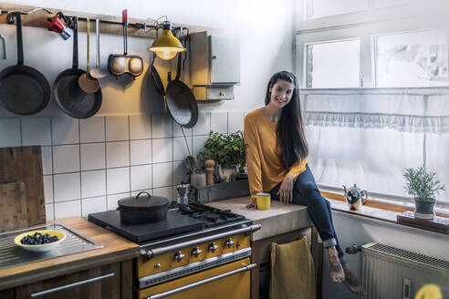 Portrait of smiling young woman sitting on kitchen counter at home - RIBF01059