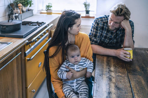 Serious family with baby sitting at kitchen table at home - RIBF01068