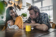 Family with baby sitting at kitchen table at home - RIBF01071