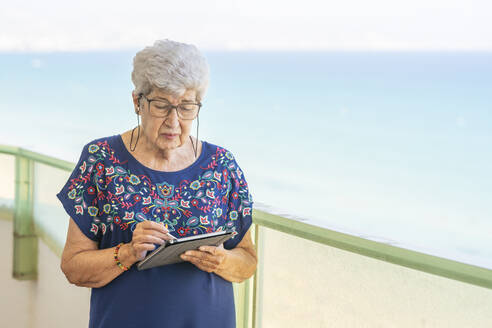 Senior woman using a tablet on a terrace - DLTSF00115