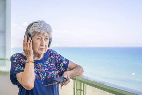 Senior woman listening music with a headphone on a terrace - DLTSF00118