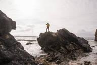 Woman wearing yellow rain jacket standing at rocky beach - UUF18965