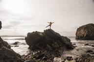 Woman wearing yellow rain jacket standing at rocky beach - UUF18968
