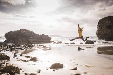 Woman jumping at the beach - UUF18971