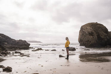 Woman wearing yellow rain jacket standing at rocky beach - UUF18974