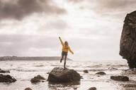 Woman wearing yellow rain jacket standing on rock - UUF18977