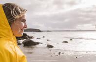 Woman wearing yellow rain jacket standing at rocky beach - UUF18980