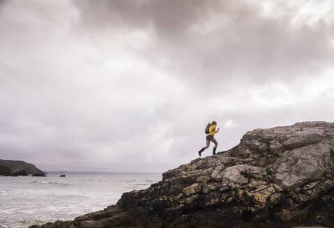Woman wearing yellow rain jacket walking at the beach - UUF18986