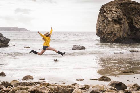 Woman jumping at the beach - UUF18989