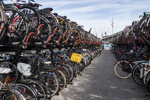 Bicycles parked at parking station in city against sky, Amsterdam, Netherlands - MEL00207