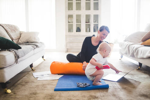 Smiling mother looking at daughter pointing at laptop while practicing yoga in living room - MASF13444