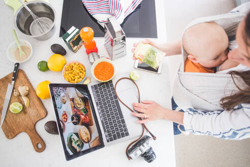 High angle view of female influencer food blogging while breastfeeding baby girl in kitchen - MASF13459