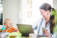 Cheerful businesswoman playing with daughter while running business from home office - MASF13477
