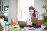 Female professional holding file while using laptop by daughter on dining table at home office - MASF13480