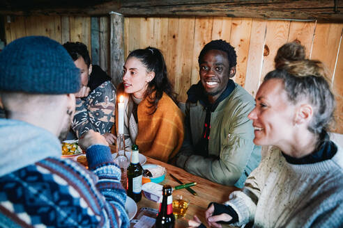 Portrait of young man sitting with friends talking while having food in log cabin - MASF13576