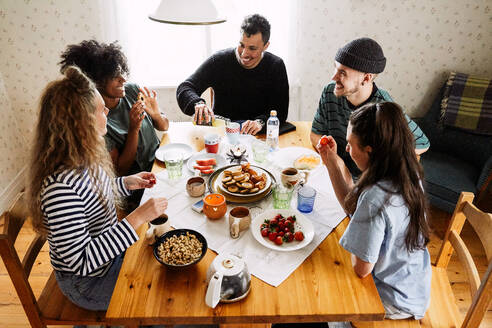 High angle view of happy friends enjoying food served on table at home - MASF13657