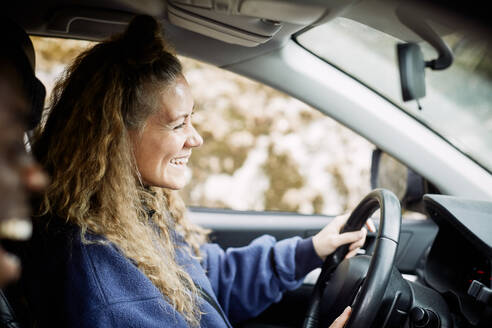 Side view of happy young woman driving car - MASF13675