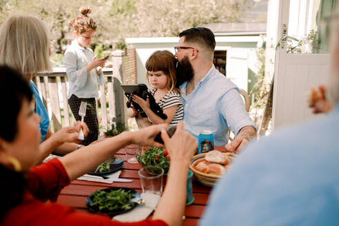 Multi-generational family having food while daughters using technology at patio - MASF13693