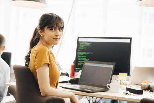 Portrait of female programmer using laptop while sitting at desk in office - MASF13804