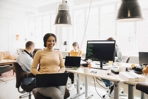 Portrait of smiling female programmer using laptop while coworkers working in background - MASF13828