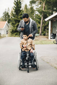 Father using smart phone while pushing autistic son on wheelchair - MASF13870