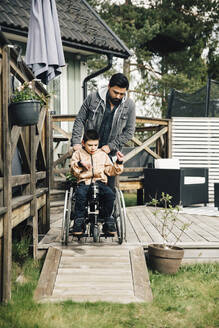 Father pushing autistic son sitting on wheelchair in yard - MASF13876