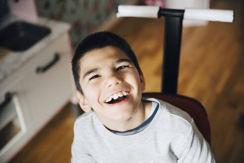 High angle view of happy disabled boy sitting on wheelchair at home - MASF13888