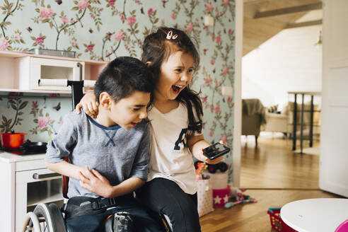 Cheerful sister watching video with autistic brother on smart phone at home - MASF13894