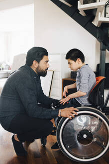 Side view of father looking at autistic son sitting on wheelchair at home - MASF13897