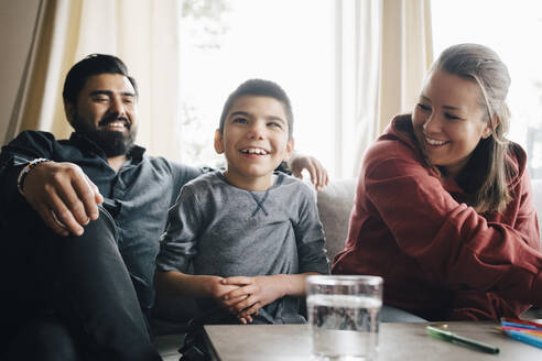 Smiling parents looking at autistic son while sitting on sofa in living room - MASF13912