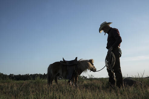 Cowboy with saddled pony in sunny rural field - FSIF04431