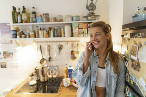 Smiling young woman on cell phone in kitchen at home - GUSF02468