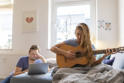 Young woman at home playing guitar with damaged string with partner using laptop - GUSF02486