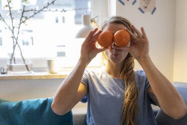 Playful young woman covering her eyes with oranges at home - GUSF02498