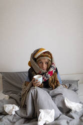 Ill young woman drinking tea in bed at home - GUSF02522