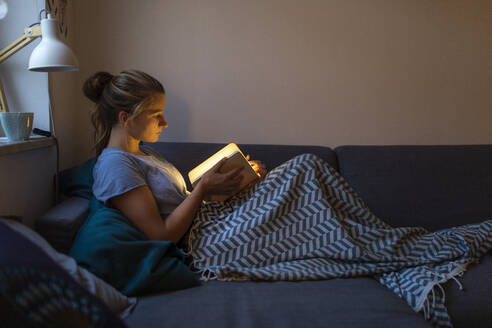 Young woman reading illuminated book on couch at home - GUSF02531