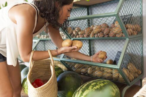 Young woman in organic store, choosing potatoes - JPTF00289