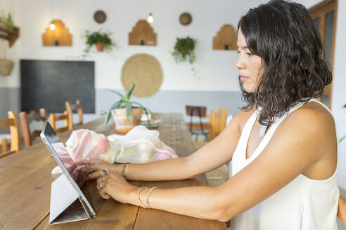 Young woman in organic store, using tablet - JPTF00292