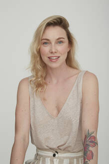 Portrait of blond tattooed woman wearing summer fashion - PGCF00002