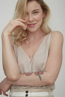 Portrait of smiling blond woman with tattoo on forearm - PGCF00005