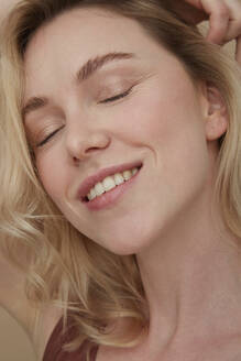 Portrait of happy blond woman wearing with eyes closed - PGCF00011