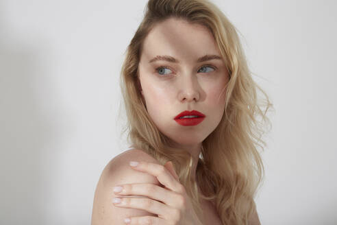 Portrait of young blond woman with red lips and shadow on her face - PGCF00017