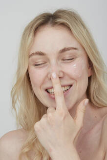 Portrait of laughing young woman applying cream on her face - PGCF00020