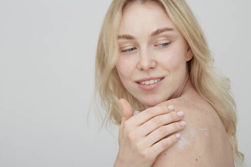 Portrait of blond young woman applying cream on her shoulder - PGCF00023